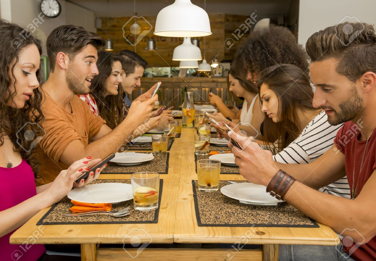 43061868-group-of-friends-at-a-restaurant-with-all-people-on-the-table-occupied-with-cellphones.jpg