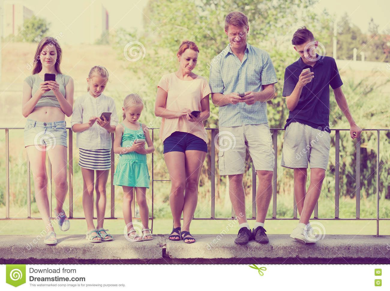 family-kids-playing-mobile-phones-four-town-summer-day-78340170.jpg