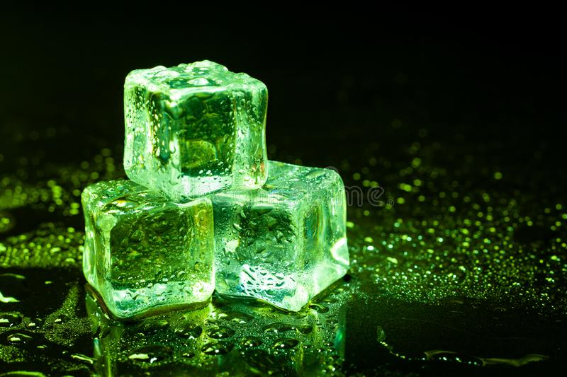 green-ice-cubes-reflection-black-table-145078250.jpg